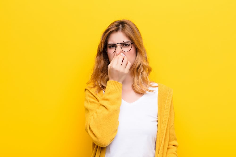 Bad Breath Causes & Solutions - Woman Holding Nose